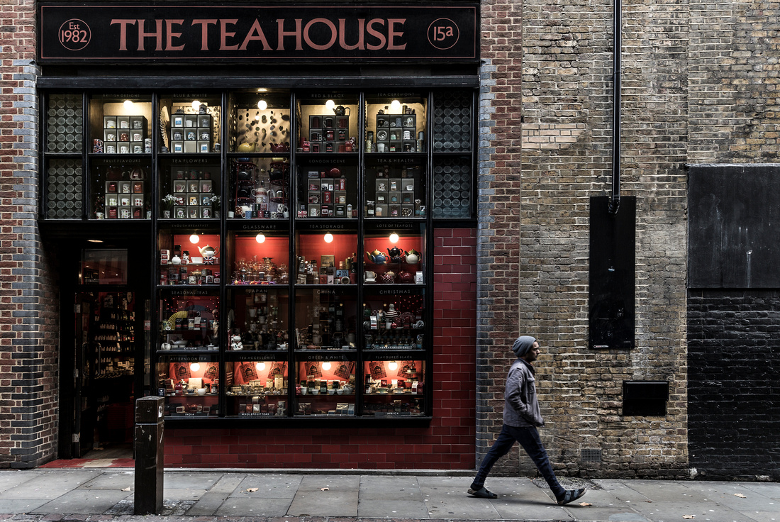 An images of a man walking by the Tea House shop in London by Preston based street photographer Alf Myers